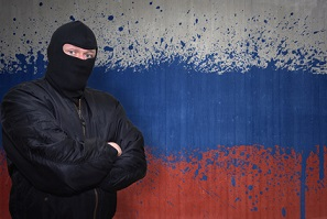 dangerous man in a mask standing near a wall with painted national flag of russia